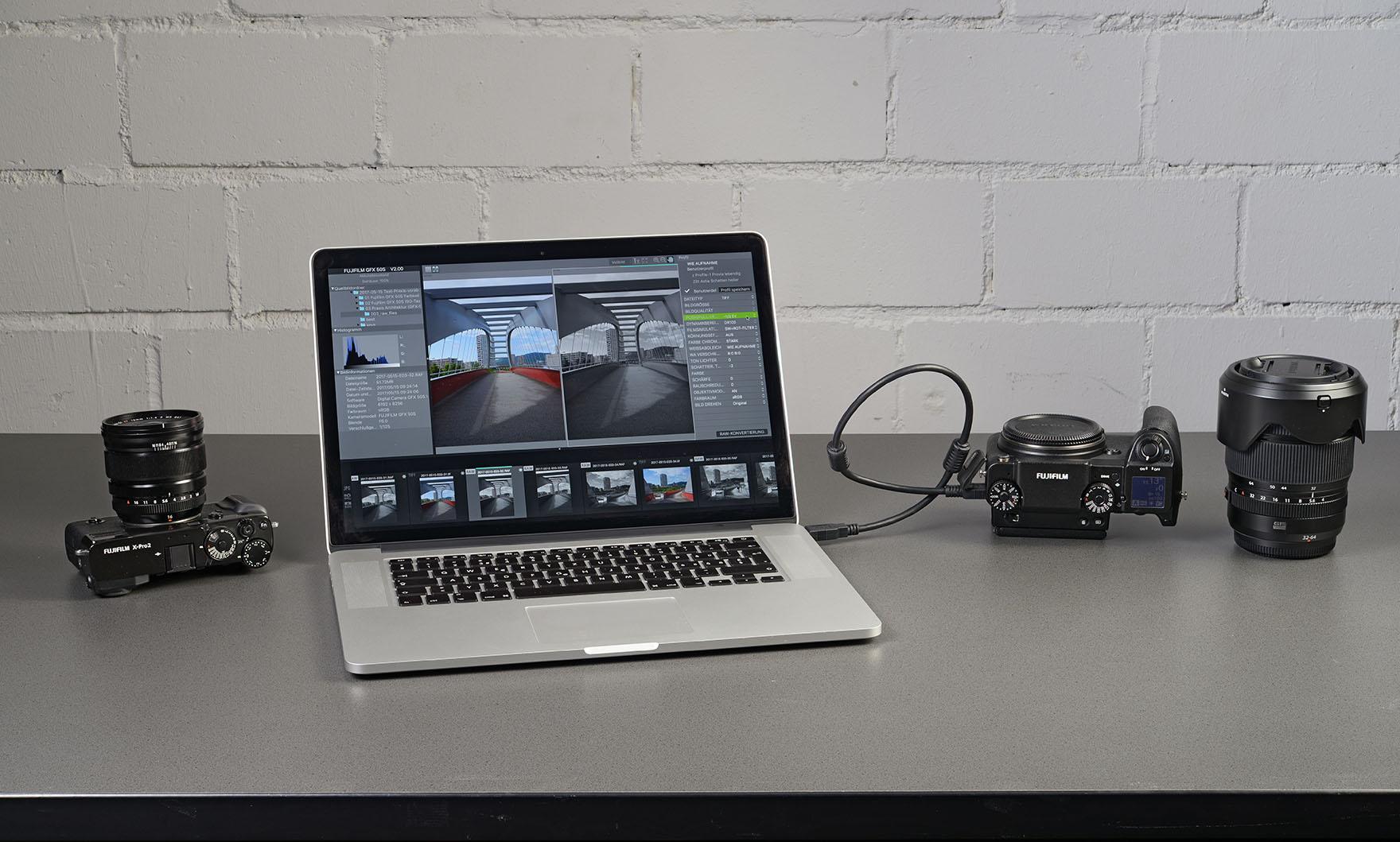 Notebook mit angezeigter Fujifilm X Raw Studio Software und flankierten Kameras Fujifilm